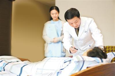 詹主任在住院部诊视手术后病人。